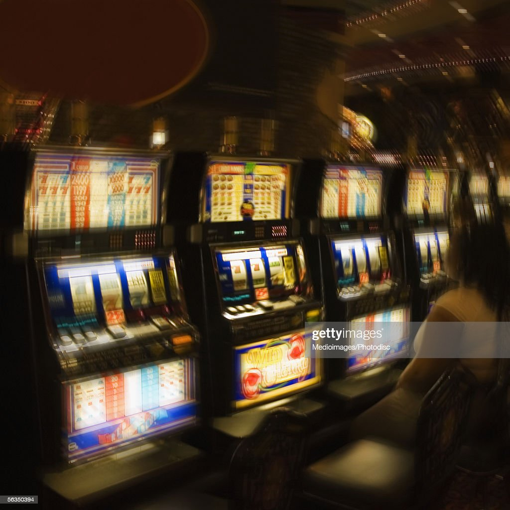 People in casino, looking at fruit machine