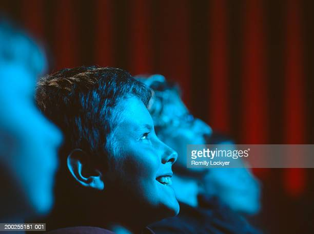People in cinema, light from screen reflected on faces (focus on boy)