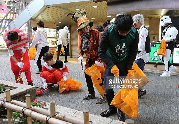 People in costumes collect garbage on the street after their Halloween party at Tokyo's Shibuya fashion district on November 1 2015 Hundreds of...