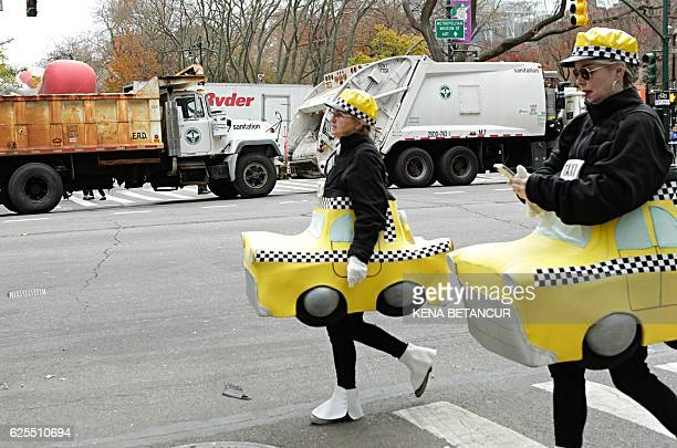 People in Customs arrive to the 90th annual Macy's Thanksgiving Day Parade as dump trucks block the streets on November 24 2016 in New York / AFP /...