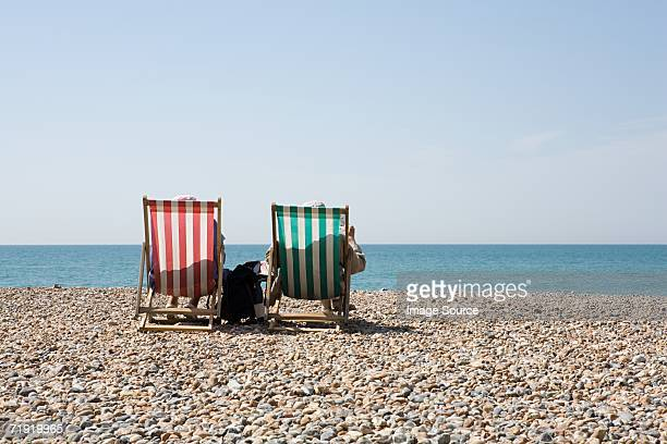 People in deckchairs at the beach