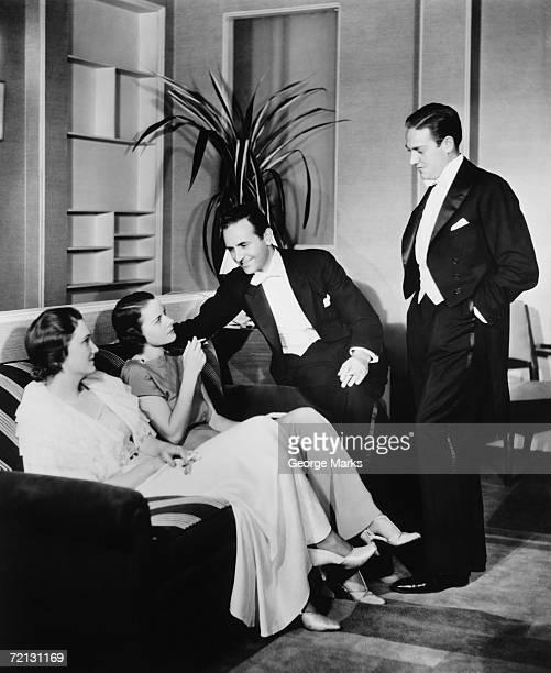 People in evening wear talking in living room (B&W)