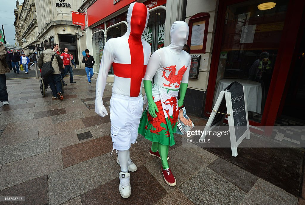 People in fancy dress, one with the flag of St George for England (L) and the other showing the Welsh dragon (R) walk along the street in Cardiff south Wales on March 16, 2013 ahead of the Six Nations international rugby union match between Wales and England at the Millennium Stadium.