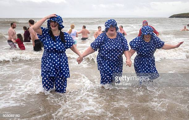 People in fancy dress run from the sea as they take part in the annual New Year's Day swim at Barry Island as several hundred swimmers marked start...