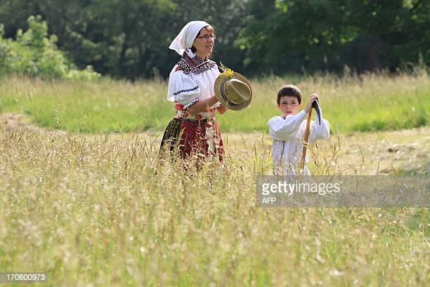 People in folk costumes are pictured with a hat and a scythe on their way to mow the meadow in Mala Vrbka 120 km southeast of Brno near the Slovakian...