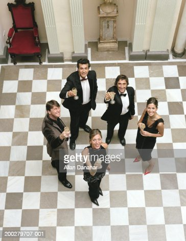 People in formal attire, raising glasses, portrait, elevated view : Stock Photo