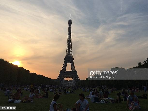 People In Front Of Eiffel Tower Against Cloudy Sky During Sunset