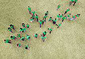 People in green t-shirts walking in field
