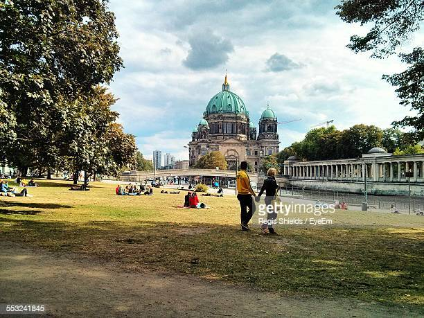 People In Lawn With Berlin Cathedral In Background Against Cloudy Sky