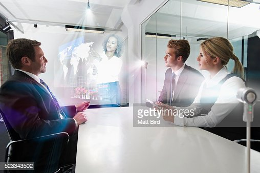 people in meeting watching holographic presentation stock