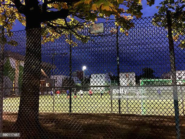 People In Playing Field Seen From Chainlink Fence