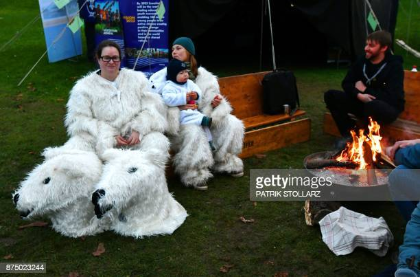 People in polar bear costumes rest next to a fire on November 16 2017 after a performance created by Danish artist Jens Galschiot during the COP23...