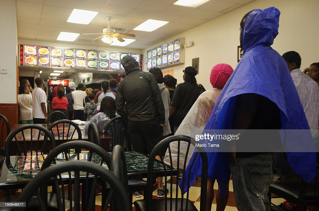 People in rain gear line up to order food in a Chinese restaurant on Canal Street that quickly reopened following the passing of the heaviest rains...
