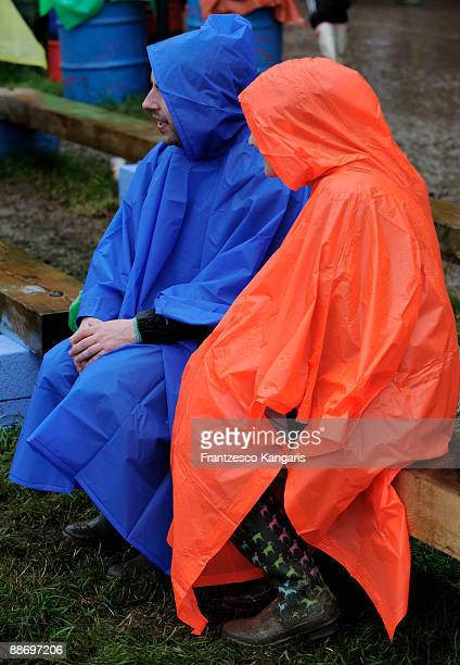 People in rain ponchos enjoy the atmosphere despite rainy weather during day two of the Glastonbury Music Festival at Glastonbury Festival site on...