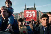 People in Red Square under banner depicting Marx Lenin and Engels