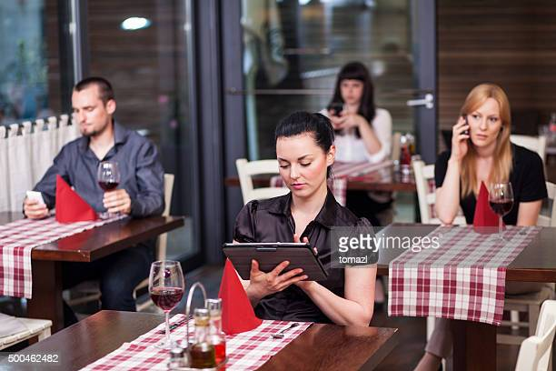 People in restaurant all using communication technology