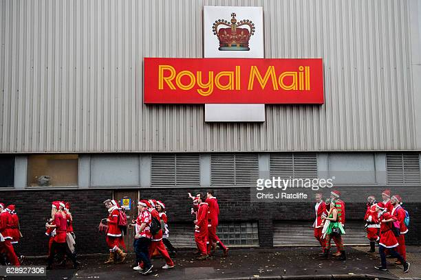 People in Santa costumes walk past a Royal Mail warehouse during the annual SantaCon on December 10 2016 in London England The event sees hundreds of...