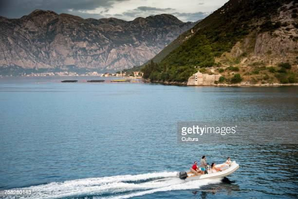 People in speedboat by mountains, Kotor, Montenegro, Europe