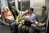 People in subway train, man resting head on woman's shoulder