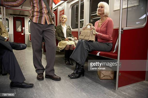 People in subway train, suspicious package hidden under seat