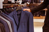 A hand of a modern young handsome businessman choosing classical suit from the row of suits in the suit shop, close-up
