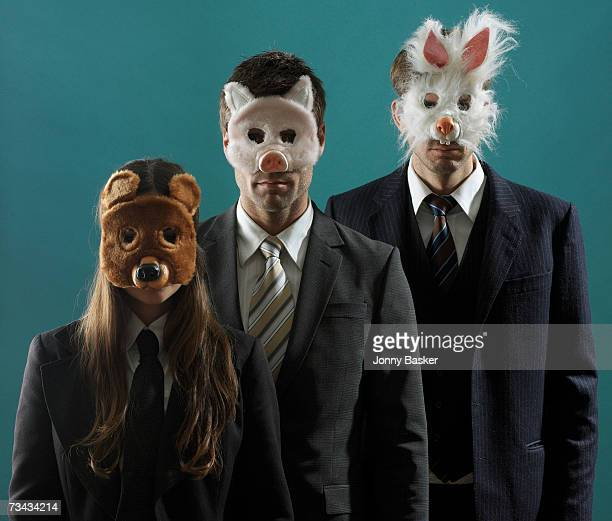 3 people in suits wearing animal masks
