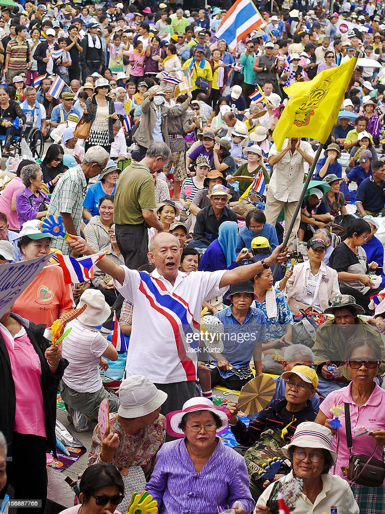 People in the crowd dance and wave Thai flags during a large anti government protest on November 24, 2012 in Bangkok, Thailand. The Siam Pitak group, which sponsored the protest, cited alleged government corruption and anti-monarchist elements within the ruling party as grounds for the protest. Police used tear gas and baton charges againt protesters.