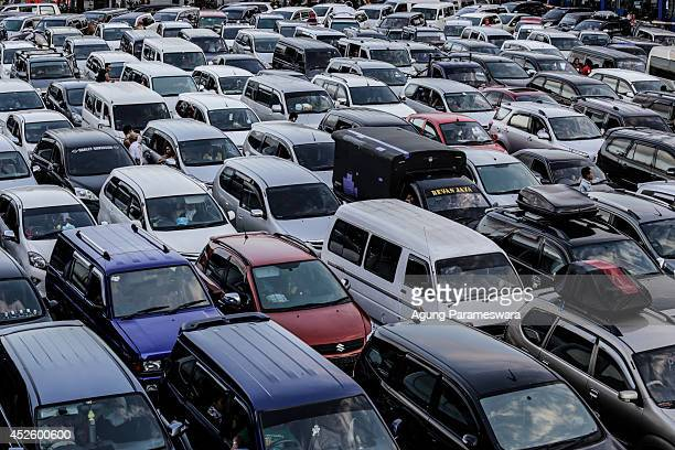 People in their cars queue to board a ferry at Gilimanuk Port on July 24 2014 in Jembrana Indonesia In the days ahead of the Eid al Fitr holiday...