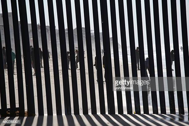 People in Tijuana Mexico walk on the beach at the USMexico border fence at Friendship Park on November 17 2013 in San Diego California The US Border...