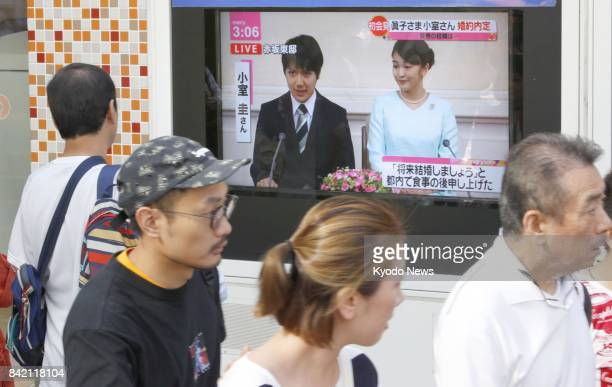 People in Tokyo watch TV coverage of Japanese Princess Mako the eldest granddaughter of Emperor Akihito and Empress Michiko and her longtime...