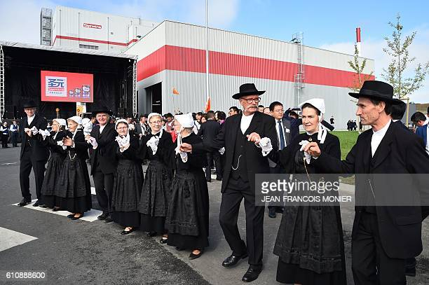 People in traditional Breton costumes perform a dance during the inauguration of the Synutra infant milk production plant in France on September 28...