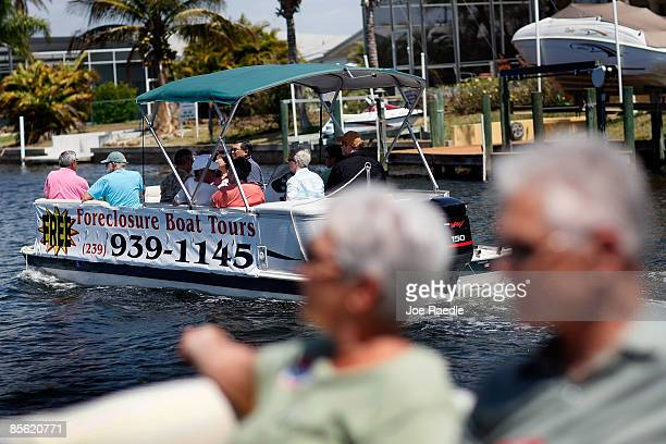 People in two boats looking to buy a home at a good price ride near each other as Foreclosures 'R Us realty company takes them on a foreclosure boat...