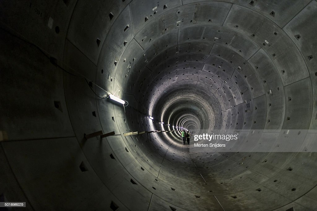 People in unfinished concrete subway pipe