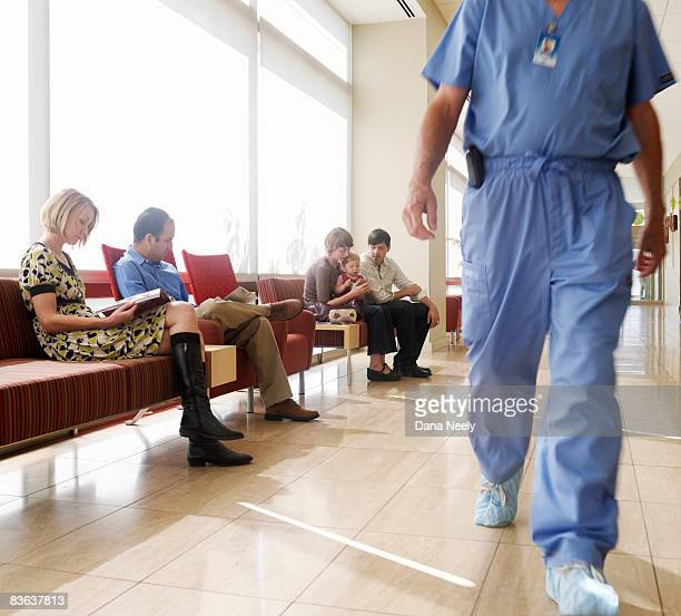 People in waiting area of hospital with surgeon wa