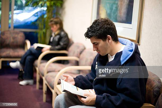 people in waiting room reading magazines