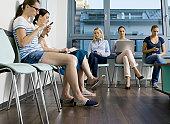 people in waiting room using digital equipment