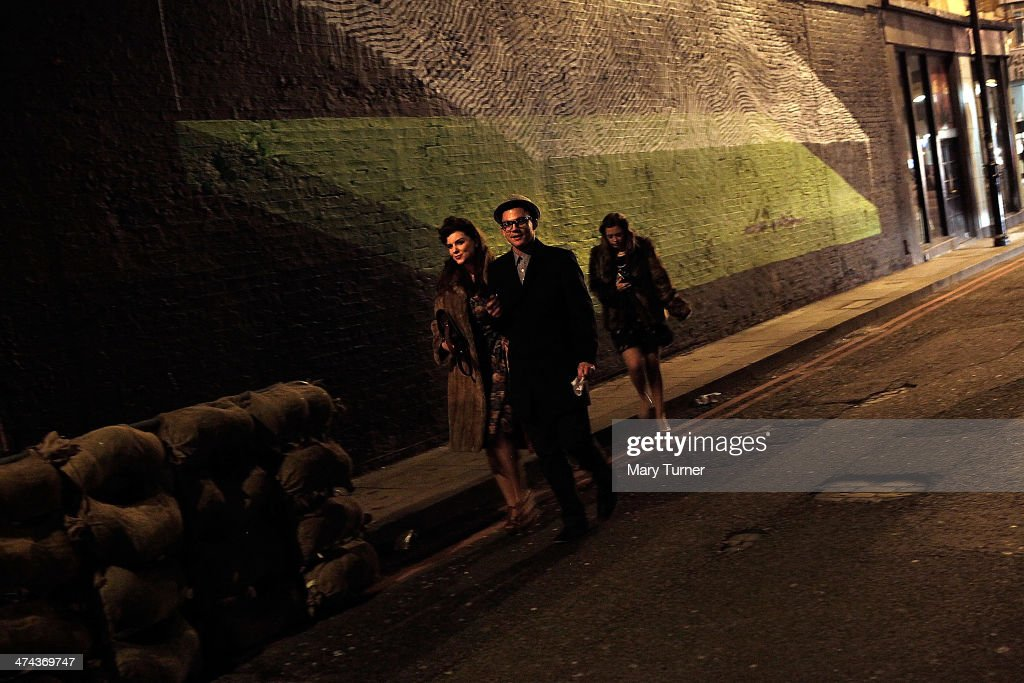 People in wartime costumes arrive on a darkened Shoreditch street to attend The Blitz Party on February 22, 2014 in London, England. Deep in an East End bunker hundreds of vintage enthusiasts partied like it was 1940 in a range of 1940s costumes, dancing to Swing and Jazz music while drinking wartime themed cocktails at The Spitfire Bar, as they embraced the glamour of and nostalgia for the era.