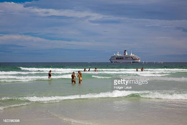 People in water at beach with cruise ship