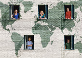 People in windows in a wall with a world map
