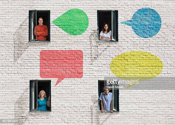 People in windows in a wall with speech-bubbles