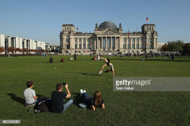People including a little girl showing off her gymanstics skills relax in front of the Reichstag seat of the Bundestag on October 17 2017 in Berlin...