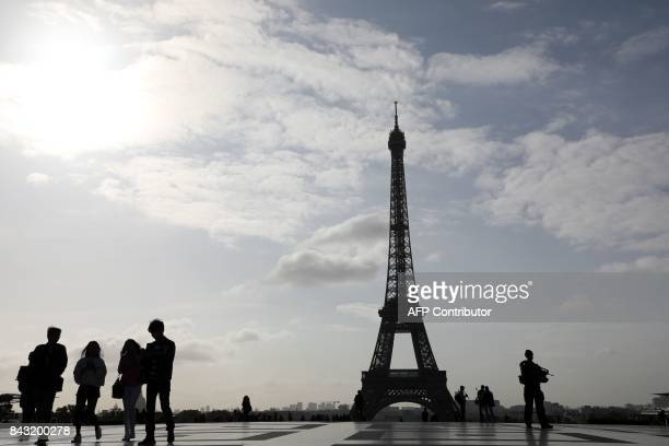 People including a soldier on the Sentinelle military force security mission walk at sunrise on the Human Rights square in front of the Eiffel tower...
