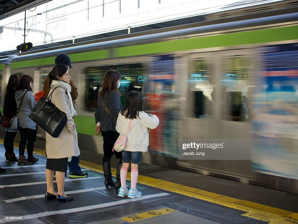 CONTENT] People, including a woman in a surgical mask and a young girl, line up at Shinjuku Station, the world's busiest, to board a JR Yamanote line train. Shinjuku Ward, Tokyo, Japan. March 27, 2012.