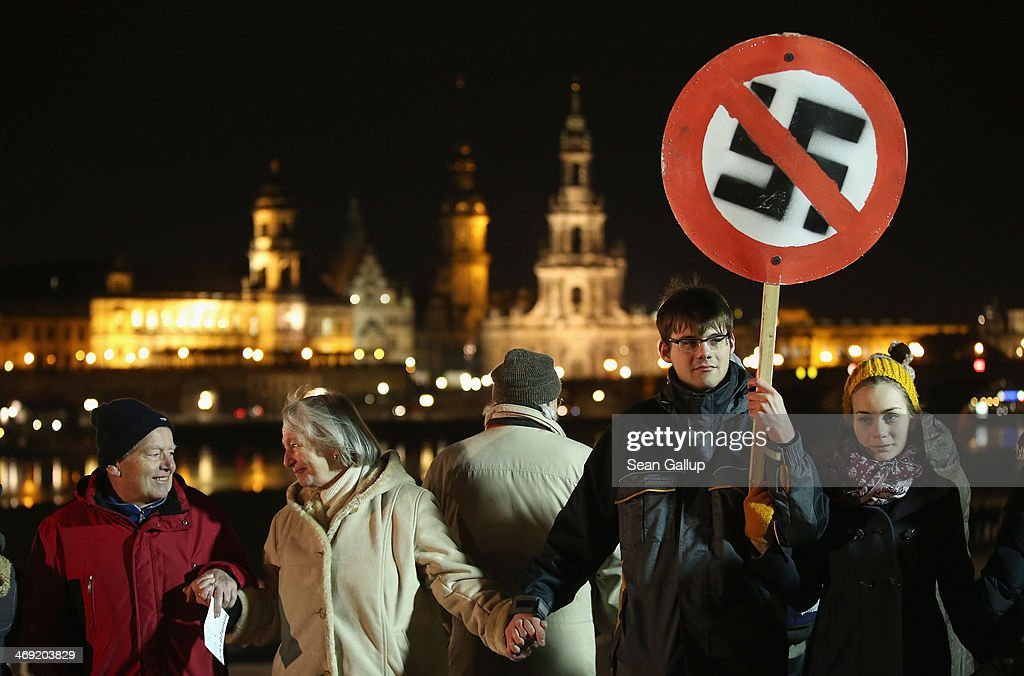 People, including one man holding a sign of a marked-through swastika, form a human chain in the city center as a statement against neo-Nazis on the 69th anniversary of the World War II firebombing of the city by the Allies on February 13, 2014 in Dresden, Germany. Neo-Nazis from across Germany have used the anniversary to parade in Dresden in recent years, though a strong, local grass movement against them has prevented their marches and this year led to the cancellation of a neo-Nazi gathering.