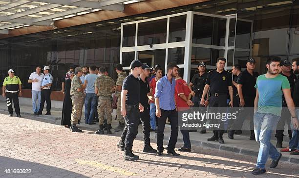 People including police officers and soldiers wait in front of an hospital for two sergeants who has wounded by the gunfire from Syria across the...