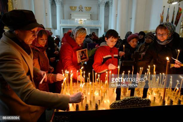 People including relatives of the victims of April 3 metro blast attend a memorial service at the Trinity Cathedral in Saint Petersburg on April 5...