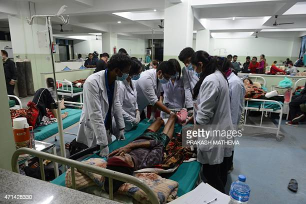 People injured in a devastating earthquake receive treatment at a hospital in Kathmandu on April 28 2015 Hungry and desperate villagers rushed...