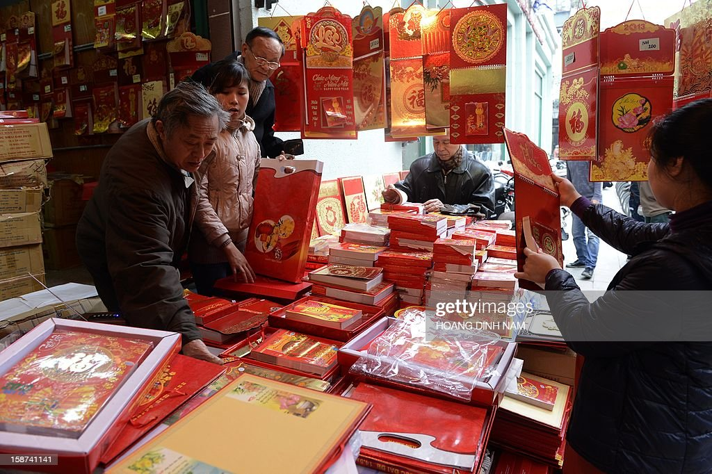 People inspect 2013 calendars on sale in front of a book store in downtown Hanoi on December 27, 2012. Vietnamese traditionally utilize calendars, allowing them to consult not only the western calendar but also the lunar calendar for important personnel and cultural events. AFP PHOTO/HOANG DINH Nam