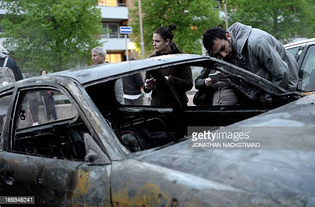 People inspect a car gutted by fire in the Stockholm suburb of Rinkeby after youths rioted in several different suburbs around Stockholm Sweden for a...