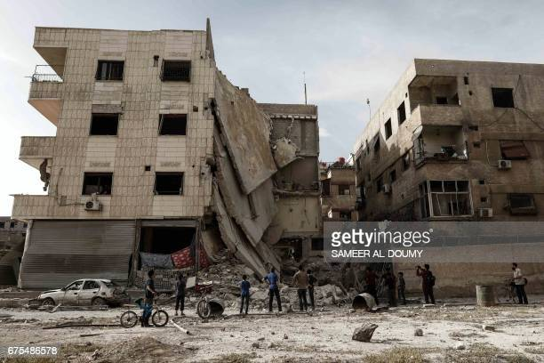 People inspect a hospital damaged following an air strike a rebelcontrolled town in the eastern Ghouta region on the outskirts of the capital...